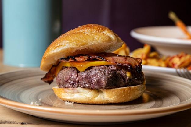 Rustykalny burger wołowy z serem i boczkiem podany na talerzu.