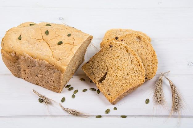 Rustykalny chleb drożdżowy pszenny z pestkami dyni na białej drewnianej powierzchni studio photo