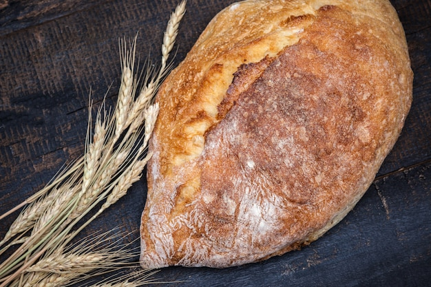 Rustykalny chleb na stół z drewna. ciemna nastrojowa przestrzeń z wolnym miejscem na tekst.