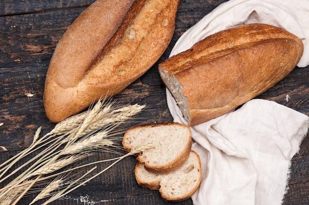 Rustykalny chleb na stół z drewna. ciemna przestrzeń drewniana
