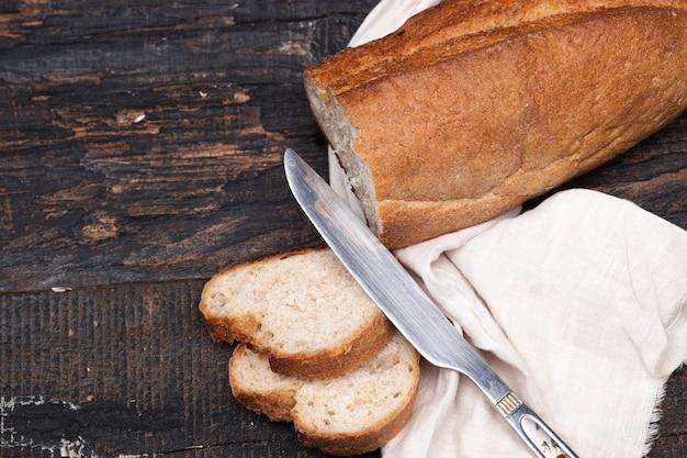 Rustykalny chleb na stół z drewna. ciemna, zadrzewiona przestrzeń z wolnym miejscem na tekst.