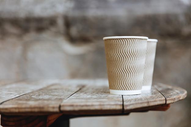 Rustykalny drewniany stół z brązowymi żebrowanymi papierowymi kubkami wypełnionymi świeżo parzoną gorącą kawą