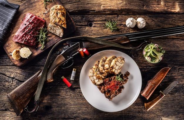 Rustykalny drewniany stół z surową sarniną, pysznym domowym kluseczkiem i rozmarynem. pomiędzy talerzem pełnym gulaszu z dziczyzny i kluskami leży pistolet myśliwski z kulami i nożem.