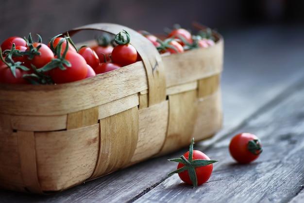 Rustykalny kosz świeżych pomidorów na drewnie