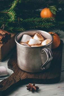 Rustykalny kubek gorącej czekolady z piankami na desce do krojenia