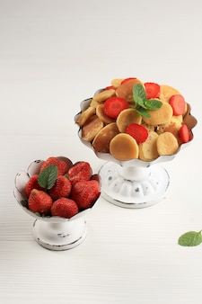 Rustykalny stojak na ciasto z malutkimi płatkami naleśnikowymi i truskawkami, przyozdobionym listkami mięty i plasterkiem cytryny na białym tle. modne jedzenie. mini naleśniki zbożowe. zdjęcie portretowe