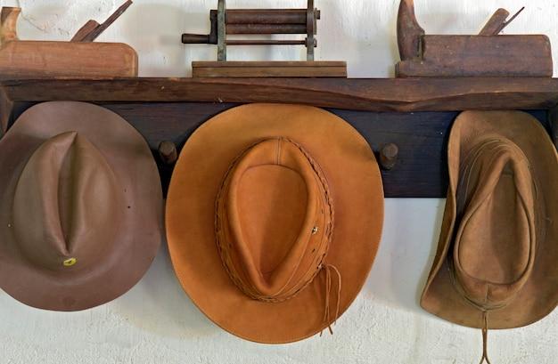 Rustykalny stojak na kapelusze ze skórzanymi czapkami