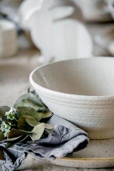 Rustykalny stół wielkanocny z pustą ceramiczną zastawą rzemieślniczą, talerzami i miskami, dekoracjami zająca wielkanocnego królika, gałązkami w wazonie na lnianym obrusie przed oknem. świąteczna kolacja wielkanocna.