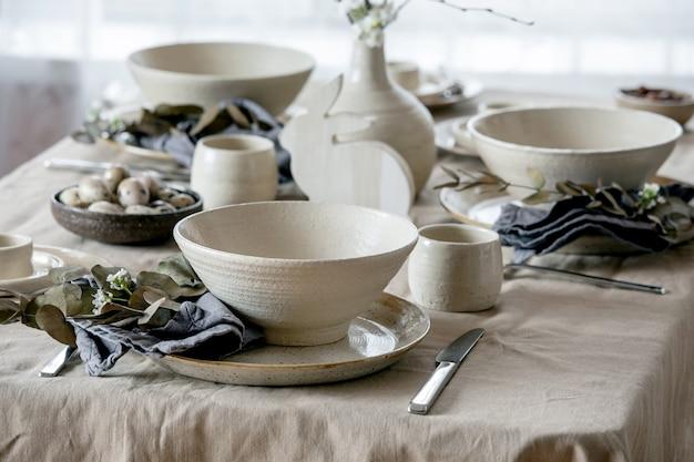 Rustykalny stół wielkanocny z pustą ceramiczną zastawą rzemieślniczą, talerzami i miskami, gałązkami w wazonie na lnianym obrusie przed oknem.