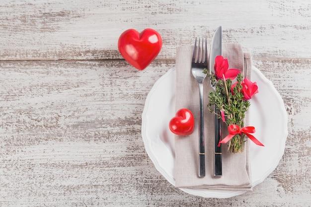 Rustykalny stół z tymiankiem i kwiatami cyklamenów oraz dekoracją w kształcie serca na jasnym drewnianym stole z copyspace