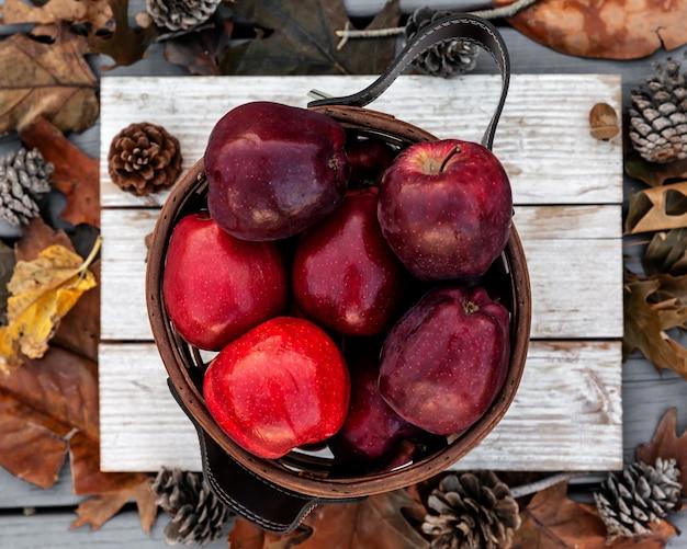 Rustykalny styl czerwonych jabłek na białym drewnianym stole