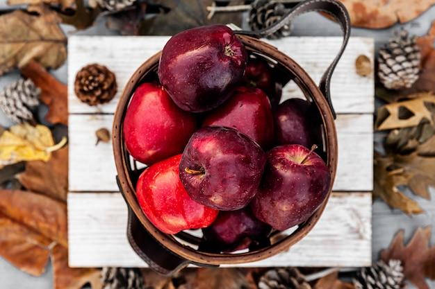 Rustykalny styl czerwonych jabłek w drewnianym koszu na białym drewnianym stole