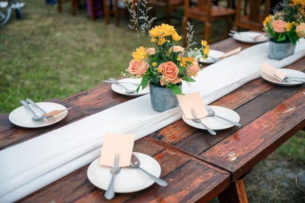Rustykalny styl ślubu, drewniany stół z dekoracją kwiatów i zastawą stołową