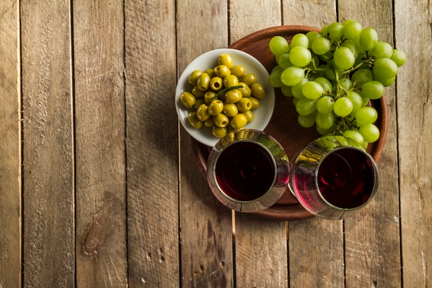 Rustykalny tła z winogron, kieliszki do wina i oliwek