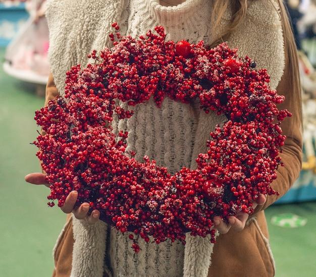 Rustykalny wieniec bożonarodzeniowy z czerwonymi jagodami w sklepie