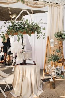 Rustykalny wystrój: kompozycja z eukaliptusa, okrągły stół z beżowym obrusem i mały dekor obok niego. dekorator stoiska