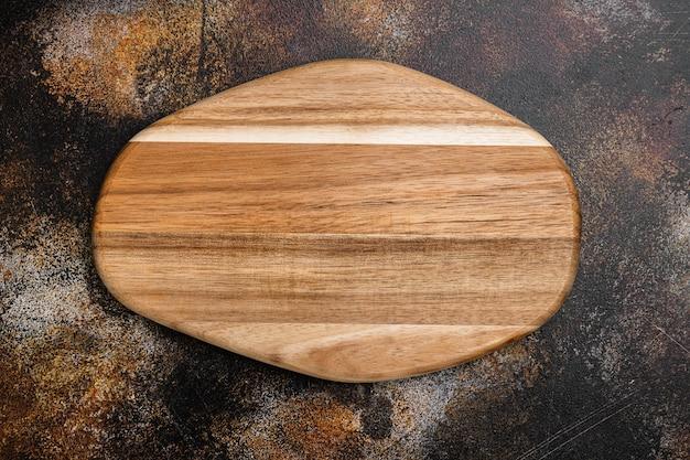 Rustykalny zestaw desek do krojenia, płaski widok z góry, z kopią miejsca na tekst lub jedzenie, na starym ciemnym rustykalnym tle stołu
