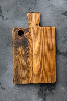 Rustykalny zestaw desek do krojenia, płaski widok z góry, z kopią miejsca na tekst lub jedzenie, na szarym tle kamiennego stołu