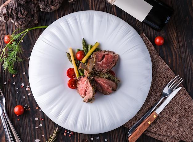 Ruszt jagnięcy z ziołami prowansalskimi na dużym białym talerzu.