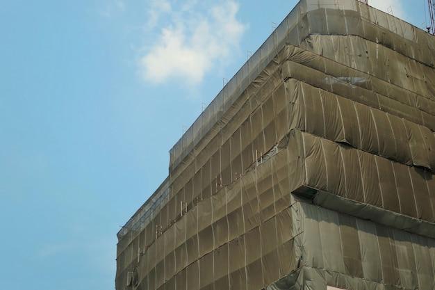 Rusztowania budowlane z szarą pokrywą przy budynku i niebieskim niebie.
