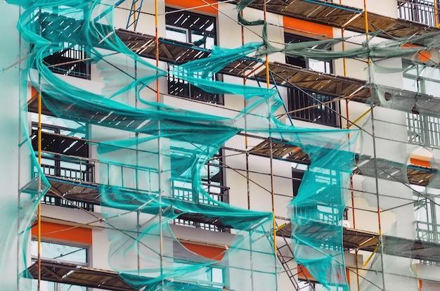 Rusztowanie na nowo wybudowanym domu i rozciągniętej zielonej siatce.