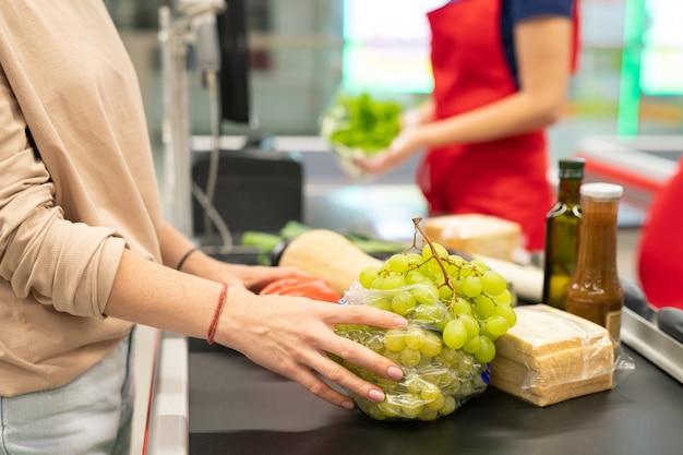 Rutyna pracy kobiety pracującej jako kasjer w nowoczesnej kasie supermarketu, ujęcie poziome