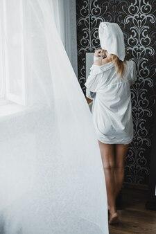 Rutynowa pielęgnacja skóry i ciała w domu młoda kobieta w piżamie i ręczniku na głowie patrzy w lustro