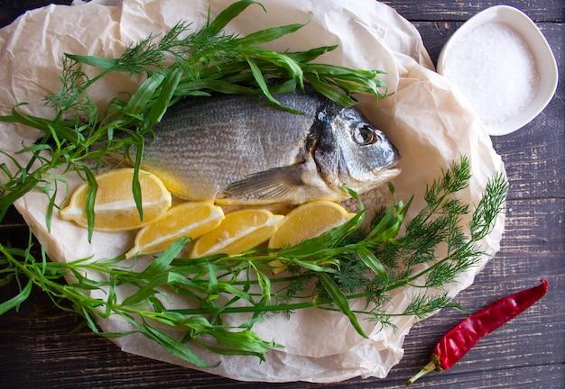 Ryba dorada z cytryną, koperkiem, rozmarynem i ostrymi papryczkami chili przygotowana do gotowania