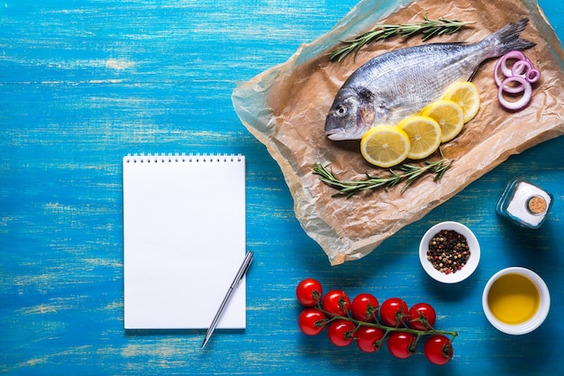 Ryba dorado na papierze do gotowania z przyprawami i zeszytem do przepisu lub menu. widok z góry na niebieskim tle.