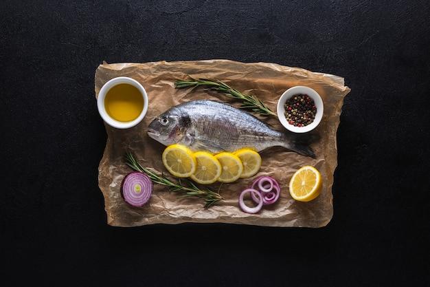 Ryba dorado przygotowana do gotowania na desce do krojenia i na pergaminie z cytryną i przyprawami. widok z góry na czarnym tle.