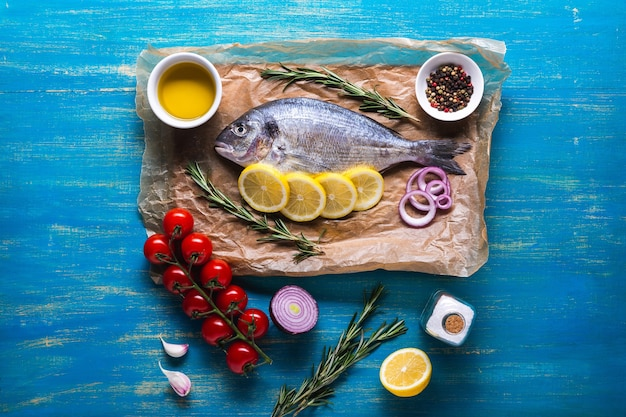 Ryba dorado przygotowana do gotowania na desce do krojenia i papierze pergaminowym z cytryną i przyprawami. widok z góry na niebieskim tle drewnianych.
