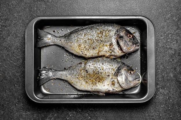 Ryba dorado surowa z przyprawami na blasze do pieczenia