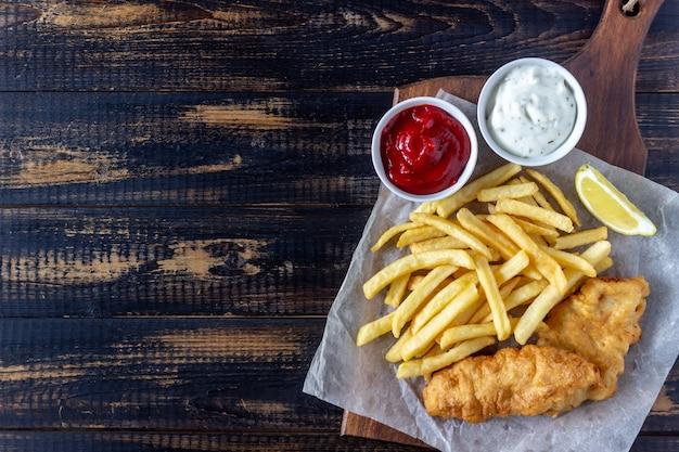 Ryba i układy scaleni na drewnianym tle. brytyjskie fast foody. przepisy przekąska do piwa. kuchnia angielska.