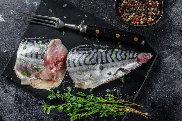 Ryba makrela wędzona na zimno z ziołami. czarne tło. widok z góry.