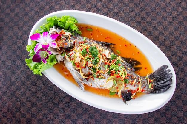 Ryba na parze z okonia morskiego z cytryną położyła białe ceramiczne naczynie na skórzanej podłodze w siatce. widok z góry.