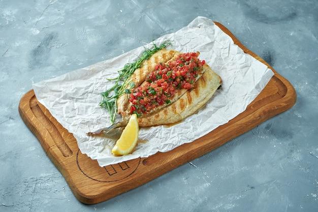 Ryba okoń morski z grilla z salsą pomidorową na drewnianej desce. gotowane owoce morza