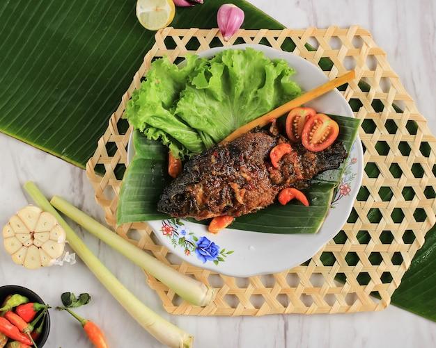Ryba pesmol przy użyciu złotej rybki. dodaj smażoną rybę do patelni. pesmol typowo rybny przepis z zachodniej jawy w indonezji o słodkim, kwaśnym i pikantnym smaku