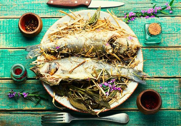 Ryba pieczona w ziołach i sianie łąkowym. pieczony okoń morski z pikantnymi ziołami