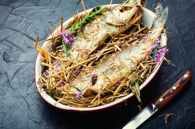 Ryba pieczona w ziołach i sianie łąkowym. pieczony okoń morski