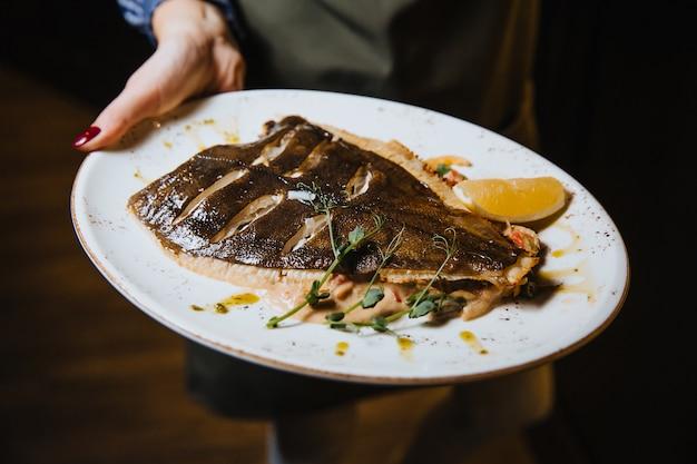 Ryba pieczona z cytryną w okrągłym talerzu