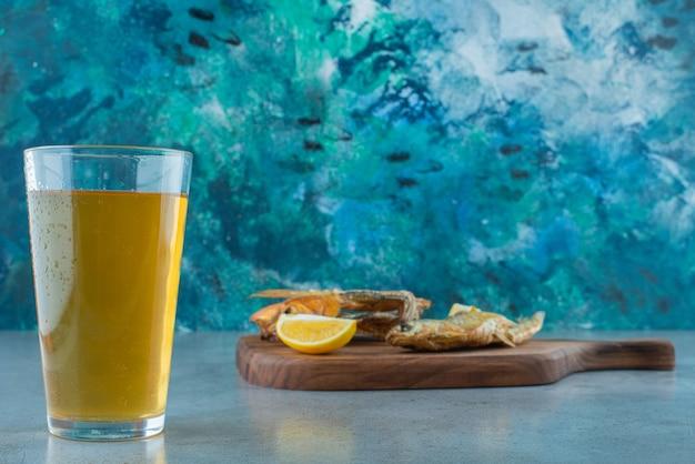 Ryba, plasterki cytryny i szklanka piwa na desce, na marmurowym stole.