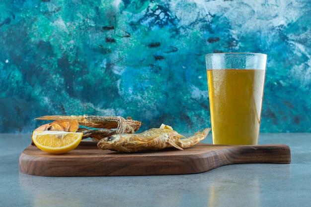 Ryba, plasterki cytryny i szklanka piwa na pokładzie na marmurze.