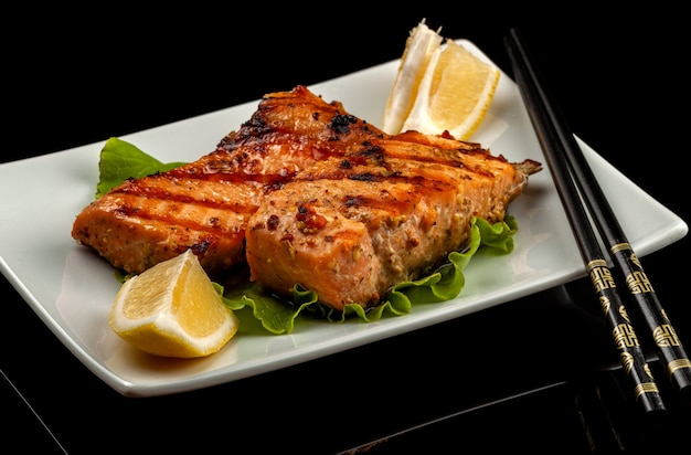 Ryba, pstrąg, kumpel łosoś, garb, kawałek pieczony, grillowany, z cytryną i sałatą