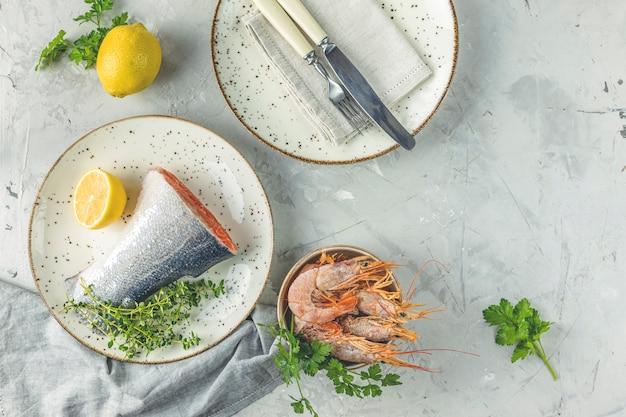 Ryba pstrągowa otoczona natką pietruszki, cytryny, krewetek, krewetek na talerzu ceramicznym. jasnoszara betonowa powierzchnia stołu