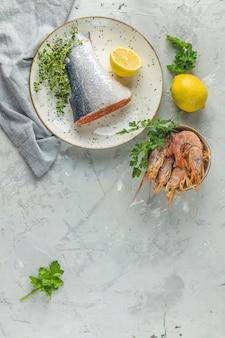 Ryba pstrągowa otoczona natką pietruszki, cytryny, krewetek, krewetek na talerzu ceramicznym