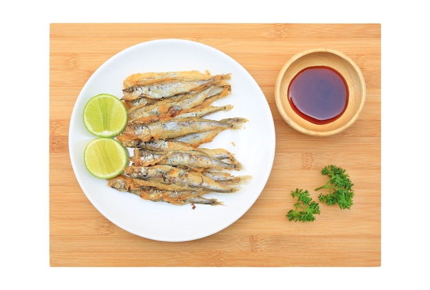 Ryba shishamo z grilla podawana z sosem cytrynowo-słodkim na tle deska
