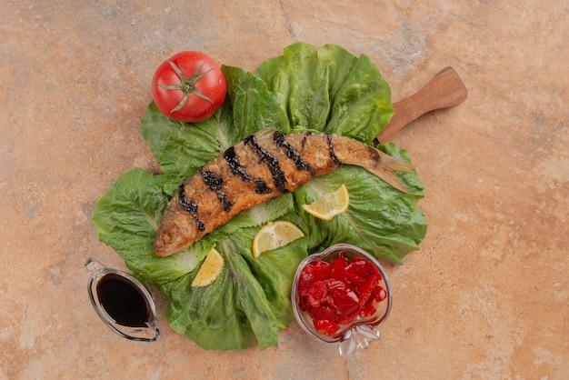 Ryba smażona na sałacie z plasterkami cytryny, piklami i sosem z granatów.