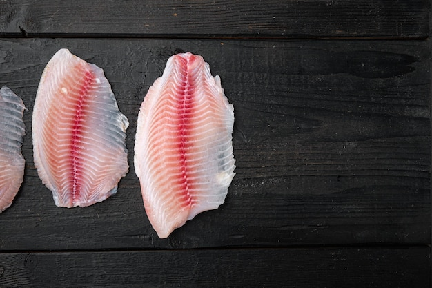 Ryba tilapia, mięso bez skóry, na czarnym drewnianym stole, widok z góry z miejscem na tekst