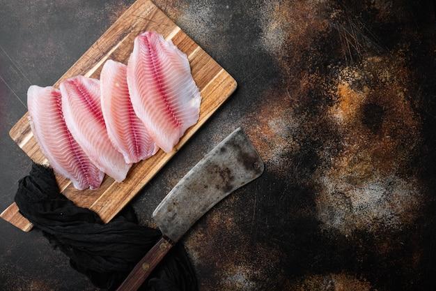 Ryba tilapia, mięso bez skóry, na starym rustykalnym tle, widok z góry z miejscem na kopię tekstu