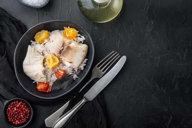Ryba tilapia z ryżem basmati i pomidorkami koktajlowymi, w misce, na czarnym tle, widok z góry z miejscem na tekst
